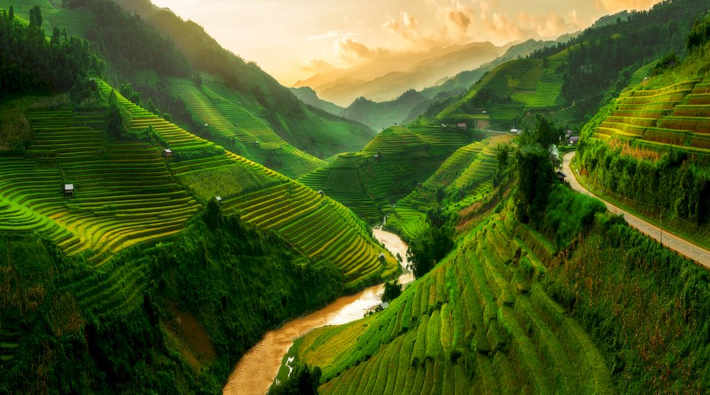 Green covered mountains surrounding a river in Asia