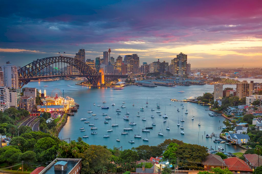 Bird's eye view of Sydney with houses, ships on the sea and a bridge