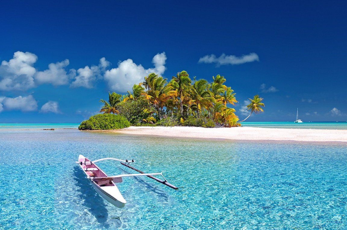 A small boat on crystal clear water in front of a small island with palm trees